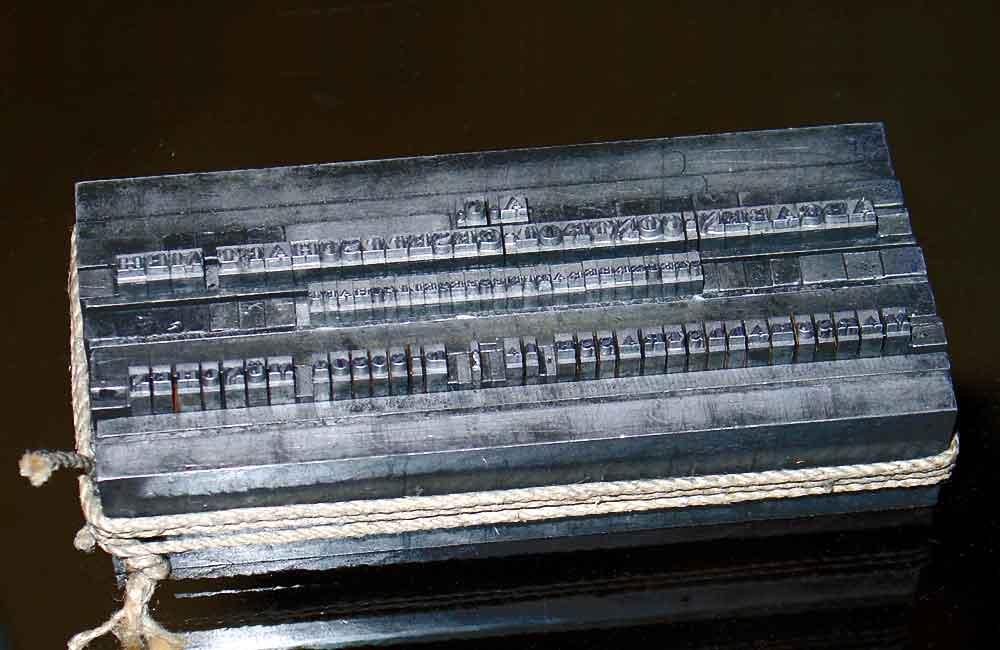Handsatzgebinde (Bleisatz) einer Empfehlungskarte vor der Drucklegung. Die oberen Majuskelzeilen sind im Normalen Breitenlauf gesetzt, die untere Zeile wurde gleichmäßig gesperrt und bei manchen Zeichenpaaren mit unterschiedlichen Spatien optisch »ausgemittelt«. Foto: Wolfgang Beinert, Berlin.
