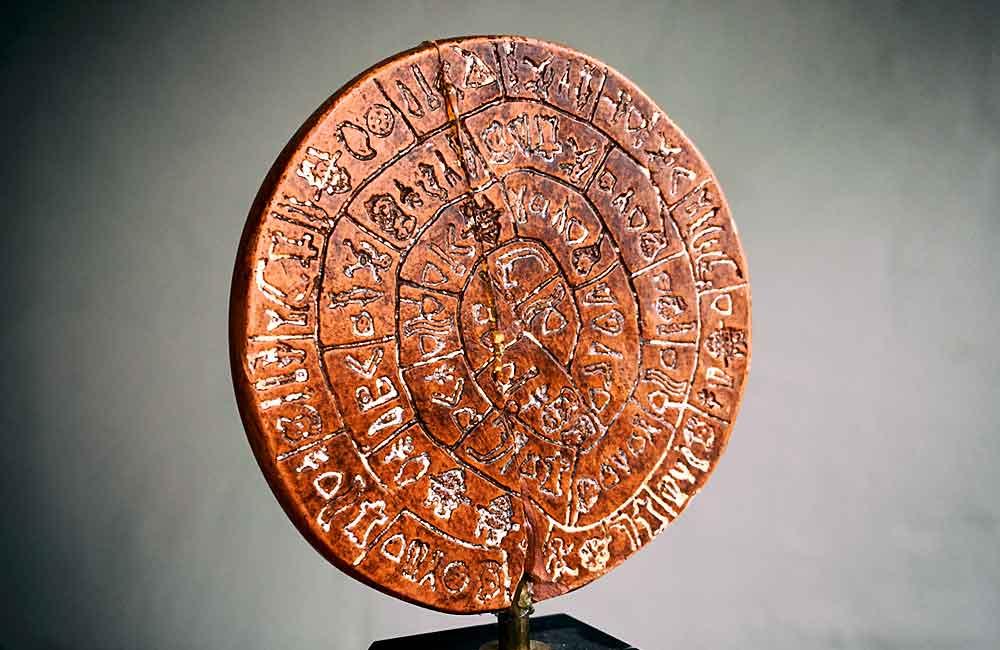 Spiraltext (beidseitig) auf dem Diskos aus dem Palastarchiv von Phaistos. Dieses auf etwa 1700 v. Chr. datierte Schriftdokument ist herstellungstechnisch betrachtet das älteste Druckwerk der Kulturgeschichte, denn die Hieroglyphenzeichen wurden mit Stempeln in den weichen Ton gepresst, bevor der Diskos hart gebrannt wurde. Quelle: Modell (beschädigt) aus der Sammlung Beinert. Das Original befindet sich im Archäologischen Museums in Iraklio auf Kreta (Griechenland).