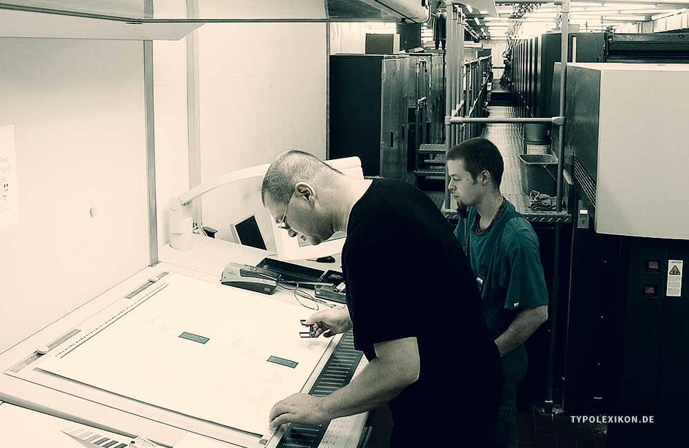 Vertrauen ist gut, Kontrolle ist besser! Der Grafikdesigner Wolfgang Beinert und sein Drucker bei der Druckabnahme des »Ersten Andrucks« an einer Originaldruckmaschine, in diesem Beispiel an einer Heidelberger Speedmaster.
