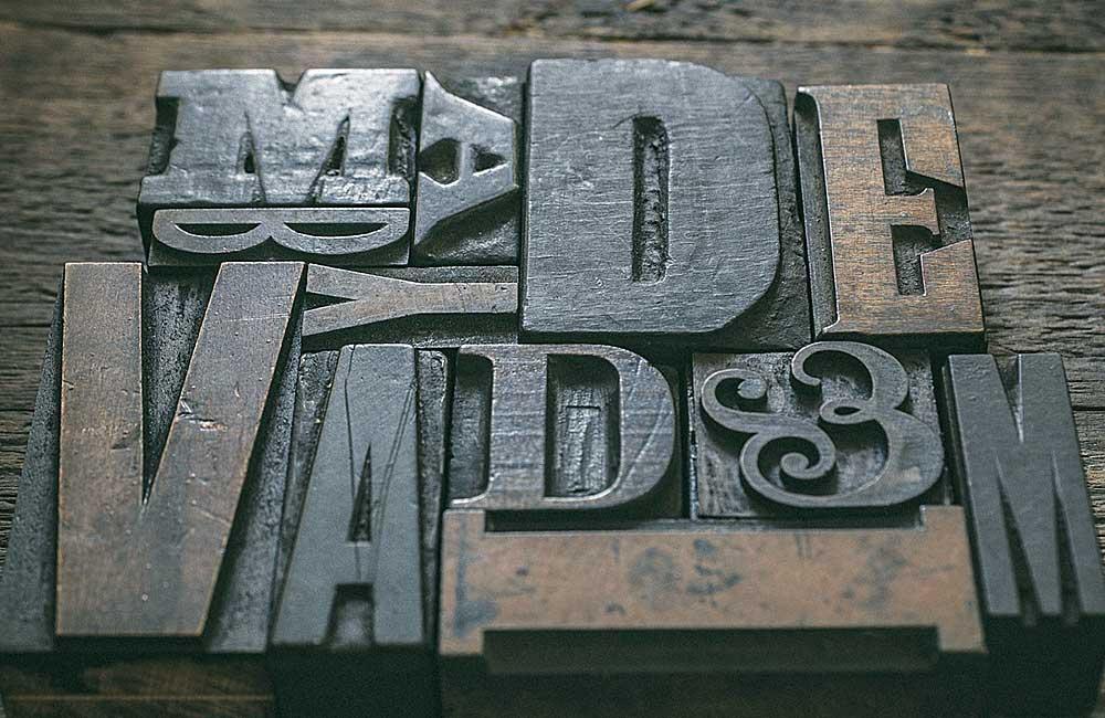 Plakatschriften sind Schriften, die aus großer Entfernung inüberdimensionierten Schriftgraden mehr oder weniger gut lesbar sind. Für den materiellen Schriftsatz mit physischen Drucktypen wurden Plakatschriften primär aus Holz (z.B. aus Buchsbaum-, Ahorn- oder Birnenholz) gefertigt, da große Buchstaben aus Metall (z.B. aus einer Blei-Zinn-Antimon-Kupfer-Legierung) in der Herstellung zu teuer und in der Verarbeitung zu unhandlich gewesen wären.Foto: pixaby.com, Hans Braxmeier & Simon Steinberger GbR, gemeinfrei.