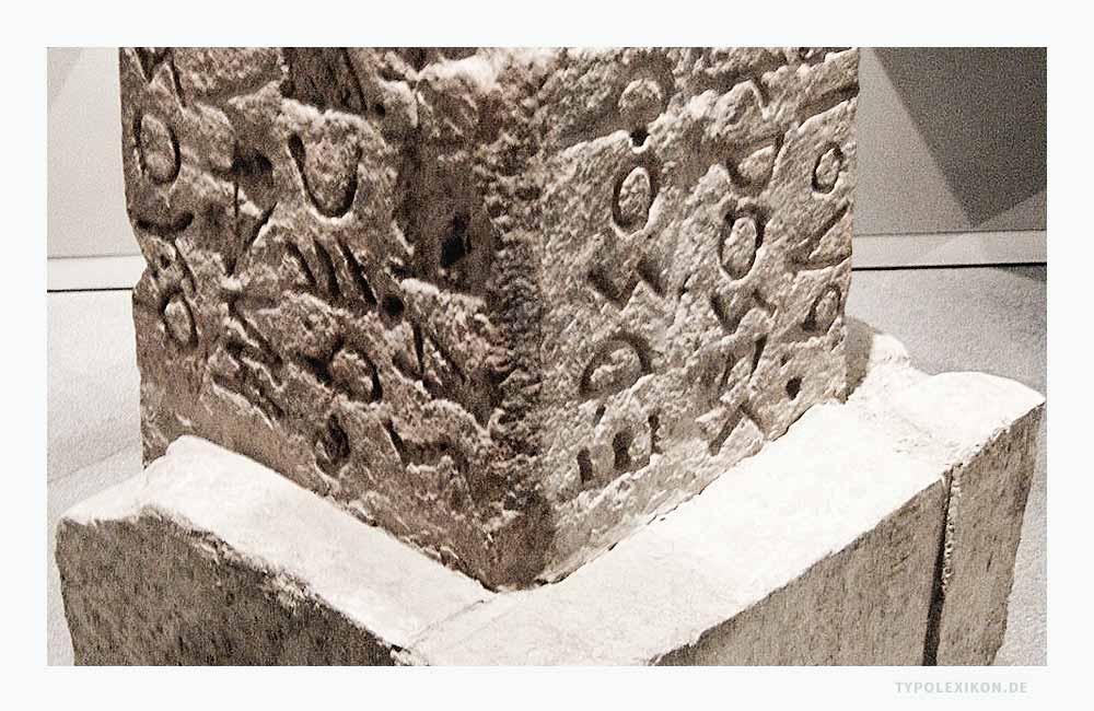 Teile der Tuffstein-Stele der Sakralstätte »Lapis Niger« auf dem Forum Romanum im Bereich des Comitium in Rom. Der Epigraph auf dem Cippus des Altars gilt als das älteste Zeugnis einer römischen »Scriptura capitalis«, dem Archetyp der Capitalis Monumentalis. Foto: Reproduktion der Stele, die am 10. Januar 1899 bei Ausgrabungen von Giacomo Boni (1859–1925) entdeckt wurde.